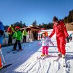 Istruttrice di sci che insegna ad una bambina piccola